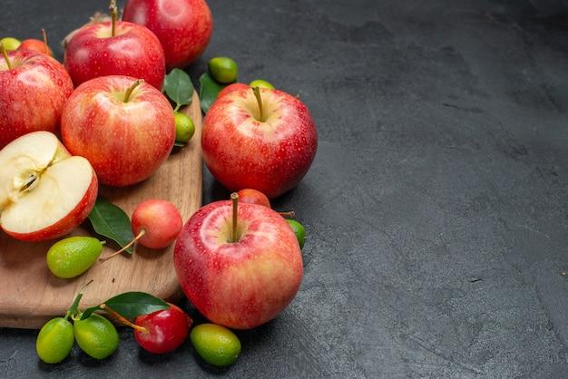 Widok z boku z bliska owoce żółto-czerwone jabłka i wiśnie z liśćmi na pokładzie owoce cytrusowe