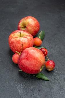 Widok z boku z bliska owocuje apetyczne jabłka i jagody z liśćmi