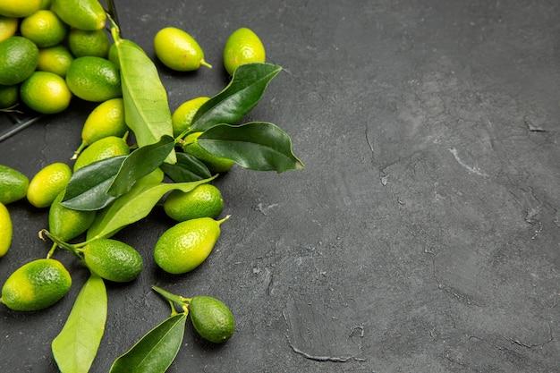 Widok z boku z bliska owocuje apetycznymi owocami z liśćmi na ciemnym stole