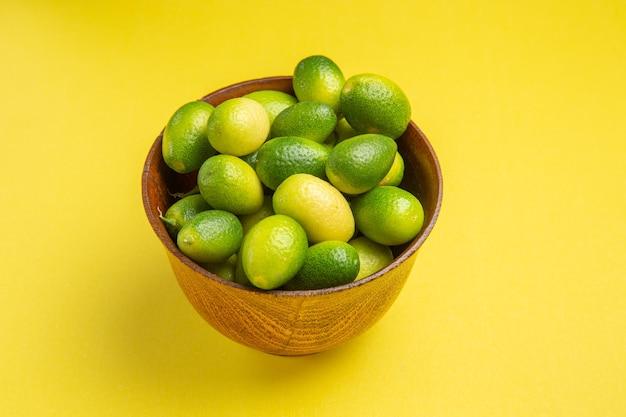 Widok z boku z bliska owocuje apetycznymi zielonymi owocami na żółtej powierzchni