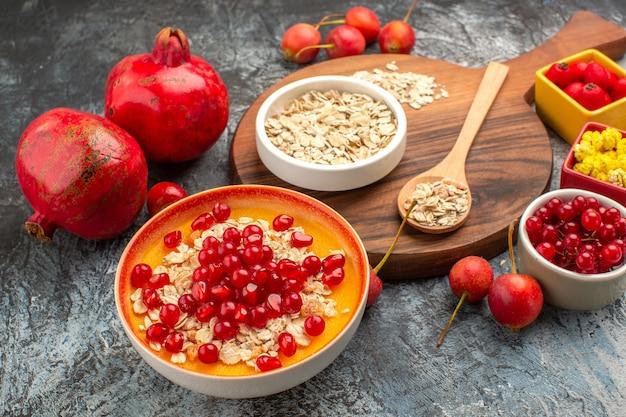 Widok z boku z bliska płatki owsiane płatki owsiane na desce granaty wiśnie czerwone porzeczki wiśnie winogrona