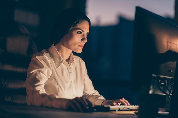 Widok z boku z bliska portret jej ładna atrakcyjna piękna skupiona skupiona inteligentna, sprytna, zapracowana pani kreatywny projektant copywriter pisanie na klawiaturze tworzenie projektu w nocy ciemne miejsce pracy stacja