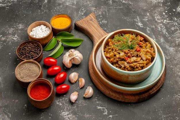 Widok z boku z bliska przyprawia fasolkę szparagową z pomidorami na desce do krojenia obok misek czosnkowych z przyprawami pozostawia pomidory na ciemnym stole