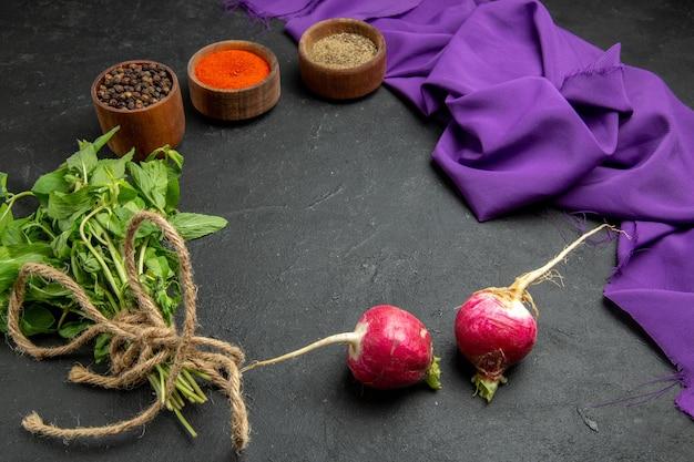 Widok z boku z bliska przyprawy kolorowe przyprawy czarny pieprz rzodkiewka zioła i fioletowy obrus