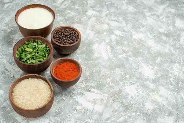 Widok z boku z bliska przyprawy ryż zioła ryż przyprawy zioła czarny pieprz i kwaśna śmietana w miskach po lewej stronie stołu