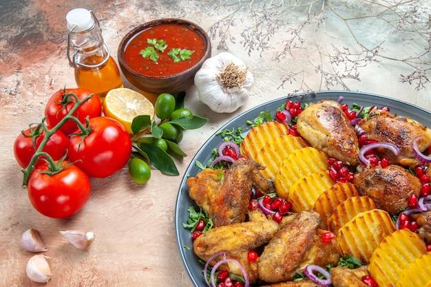 Widok z boku z bliska sos butelka pomidorów oliwy z szypułkami sos cytrynowy talerz czosnku naczynia