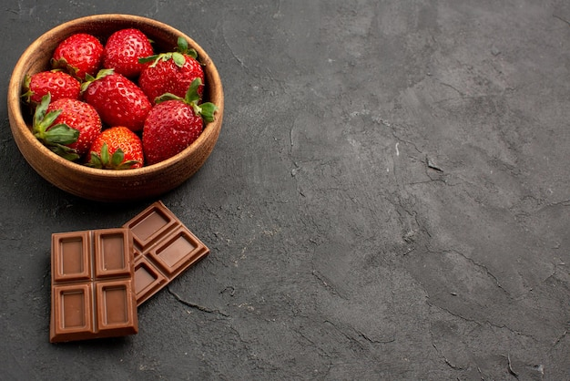 Widok z boku z bliska truskawki w misce apetyczne tabliczki czekolady obok truskawek w misce po lewej stronie ciemnego stołu