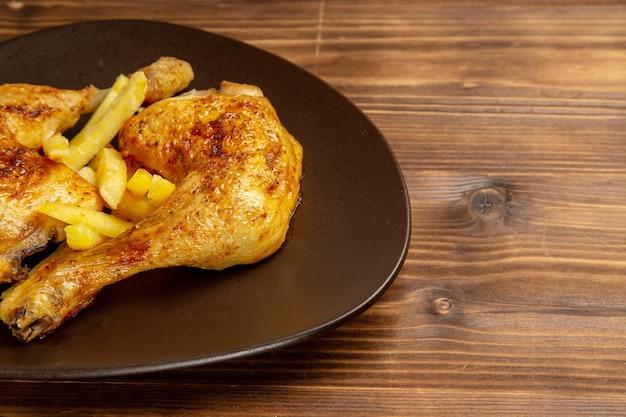 Widok z boku z bliska udka z kurczaka talerz z apetycznymi udkami z kurczaka i frytkami po lewej stronie stołu