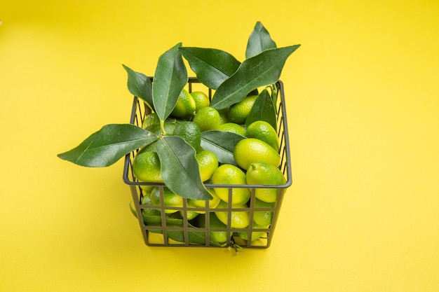 Widok z boku z bliska zielone owoce apetyczne zielone owoce z liśćmi w szarym koszu