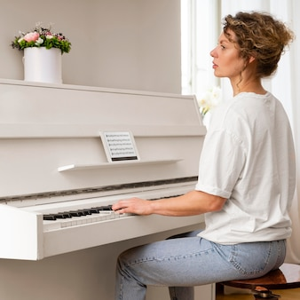 Widok z boku z blondynką grającą na pianinie