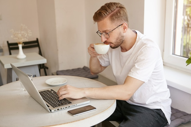 Widok z boku z brodatym ładnym facetem w białej koszulce, pije kawę i pracuje zdalnie z laptopem w miejscu publicznym, robiąc małą przerwę