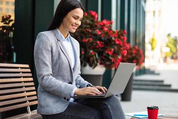 Widok z boku z businesswoman za pomocą laptopa na zewnątrz mając kawę
