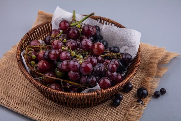 Widok z boku z czarnych winogron w koszu na worze na szarym tle