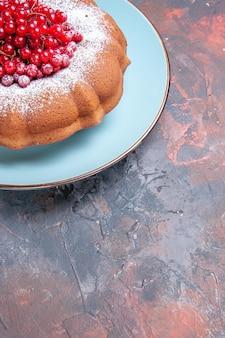 Widok z boku z daleka apetyczny tort ciasto i apetyczne czerwone porzeczki na niebieskim talerzu
