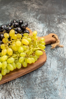 Widok z boku z daleka drewniana deska do krojenia winogron z apetycznymi zielonymi i czarnymi winogronami