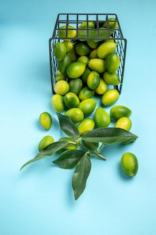 Widok z boku z daleka kosz owoców zielono-żółtych owoców cytrusowych z liśćmi na niebieskim stole