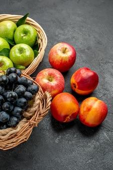 Widok z boku z daleka kosze owoców z jabłkami i kiściami winogron obok pięciu nektarynek