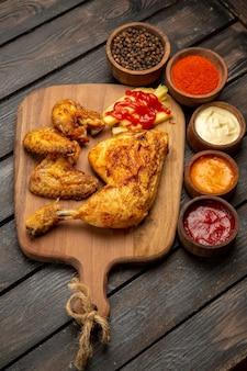 Widok z boku z daleka kurczak i sosy kurczak i frytki na drewnianej desce obok sosów z czarnego pieprzu ketchup i przypraw na stole