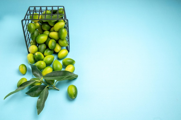 Widok z boku z daleka owoce zielono-żółte owoce z liśćmi w koszu na niebieskim stole