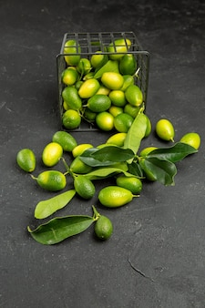 Widok z boku z daleka owocuje apetycznymi owocami z liśćmi na stole