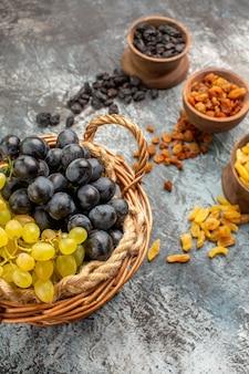 Widok z boku z daleka winogrona trzy miski suszonych owoców drewniany kosz apetycznych winogron