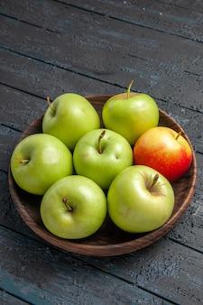Widok z boku z daleka zielono-żółto-czerwonawe jabłka drewniana miska zielono-żółto-czerwonych jabłek na szarym stole