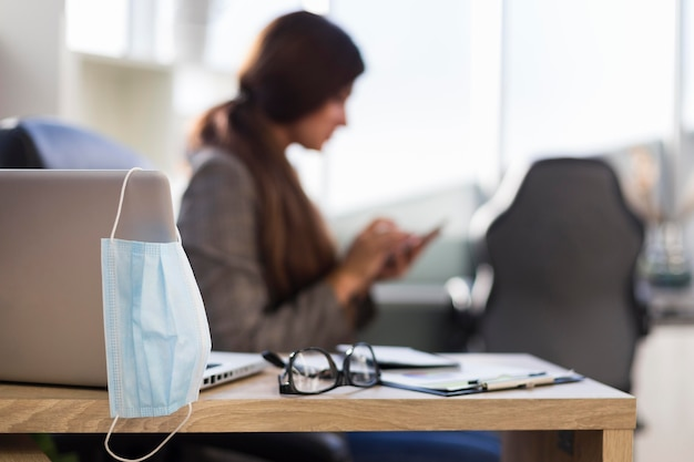 Widok z boku z defocused kobieta interesu na biurku