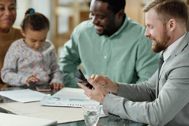 Widok z boku z eleganckim mężczyzną z kalkulatorem doradzającym młodej rodzinie etnicznej z dzieckiem na kredyt hipoteczny
