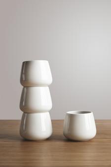 Widok z boku z góry wąskie puste białe proste filiżanki do kawy w piramidzie na grubym drewnianym stole na białym tle