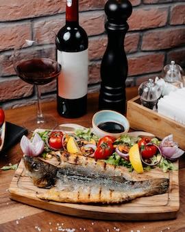 Widok z boku z grilla okonia morskiego podany ze świeżymi warzywami, sosem lemonnd narsharab na drewnianym stole