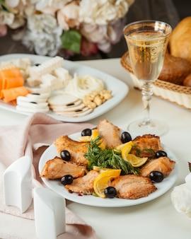 Widok z boku z grilla ryby cytryny oliwki wino