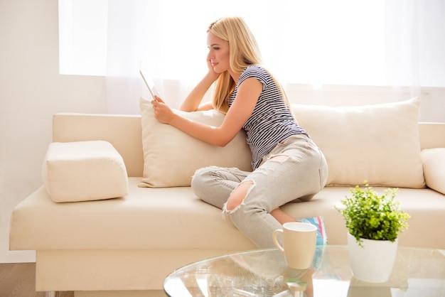 Widok z boku z ładną blondynką siedzącą na kanapie z tabletem na wakacjach