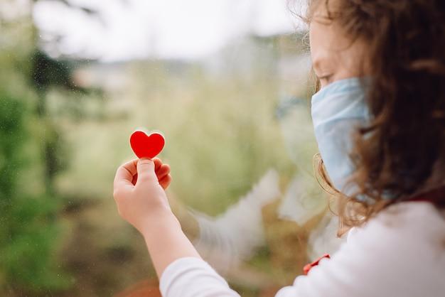 Widok z boku z małą dziewczynką w wieku przedszkolnym w noszeniu ochronnej maski, siedząc na parapecie w domu, trzymając małe czerwone serce pozostań w domu zapobieganie pandemii koronawirusa kwarantanny. kwarantanna domowa