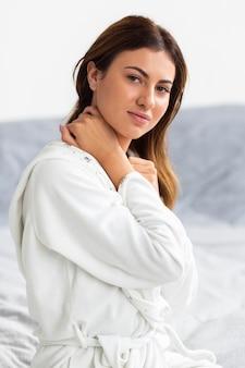 Widok z boku z piękną kobietą stwarzających w szlafroku