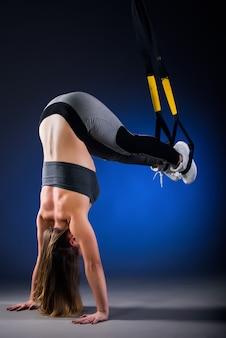 Widok z boku z piękną młodą kobietą sportowca stojącego na czarno z wiszącymi paskami.