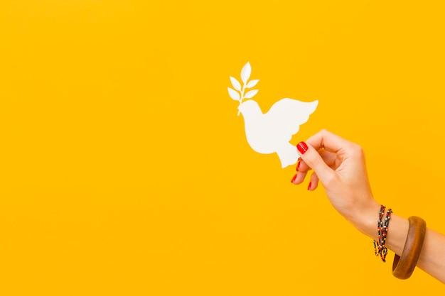 Widok z boku z ręki trzymającej papierową gołębicę