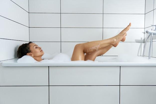 Widok z boku z sexy piękna kobieta biorąc relaksującą kąpiel z pianką w łazience