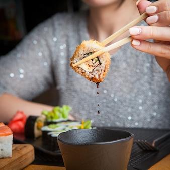 Widok z boku z sosem sojowym i pałeczką w ręce kobiety