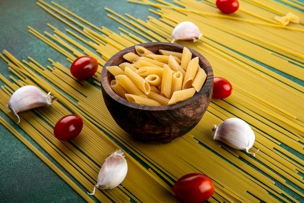 Widok z boku z surowego spaghetti z makaronem w misce pomidorkami cherry i czosnkiem na zielonej powierzchni