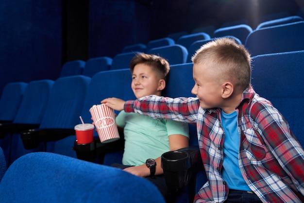 Widok z boku zabawnych chłopców oglądających razem komiczny film w kinie