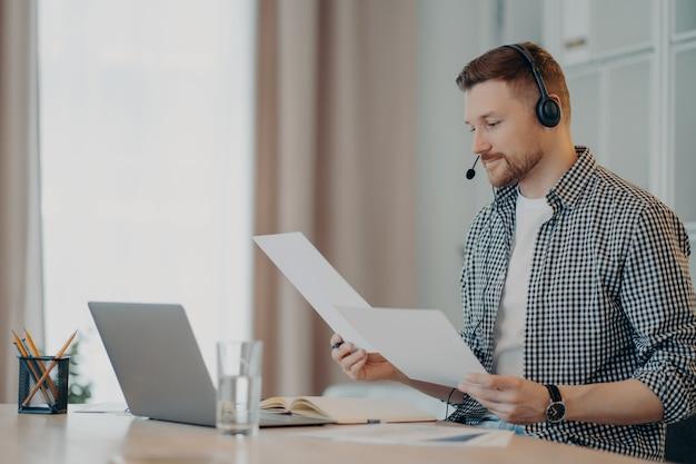 Widok z boku zajęty młody człowiek pracujący z laptopem i za pomocą zestawu słuchawkowego podczas spotkania online. mężczyzna freelancer analizujący dokumenty projektowe lub raport sprzedaży w swoim miejscu pracy. praca zdalna w domu