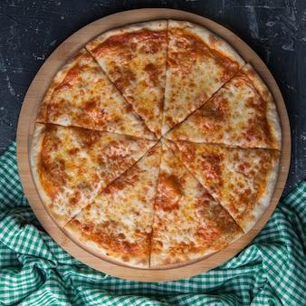 Widok z boku zamknięta pizza z szmatką w kratkę w okrągłej desce