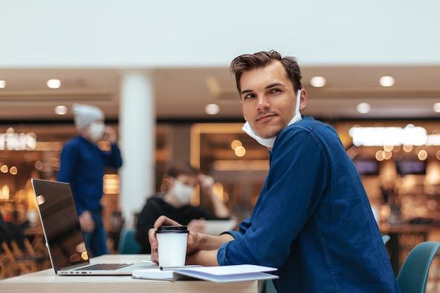 Widok z boku. zamyślony młody człowiek siedzący przy stole w kawiarni