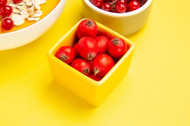 Widok z boku zbliżenie jagody miski płatków owsianych jagody na żółtym stole