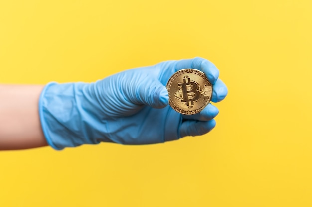 Widok z boku zbliżenie ludzkiej dłoni w niebieskich rękawiczkach chirurgicznych, trzymając w ręku i pokazując symbol bitcoina.