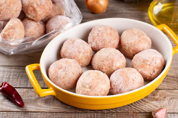 Widok z boku zbliżenie na surowe półprodukty mrożone klopsiki w naczyniu do pieczenia z ryżem, cebulą i mięsem, poziome