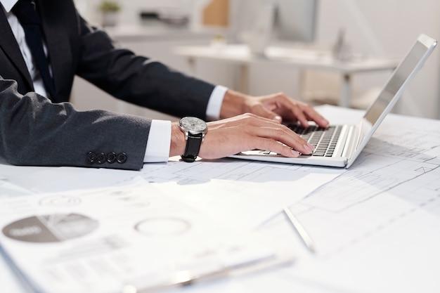 Widok z boku zbliżenie nie do poznania biznesmen sukcesu za pomocą laptopa w miejscu pracy