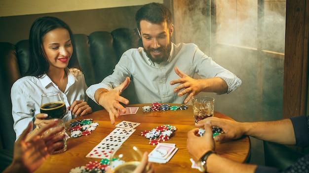 Widok z boku zdjęcie przyjaciół płci męskiej i żeńskiej siedzi przy drewnianym stole.
