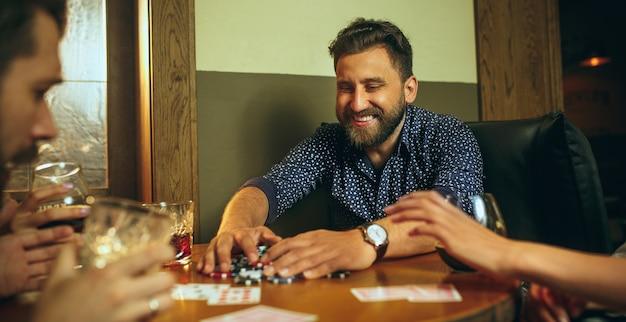 Widok z boku zdjęcie przyjaciół siedzących przy drewnianym stole. przyjaciele bawią się podczas gry planszowej.