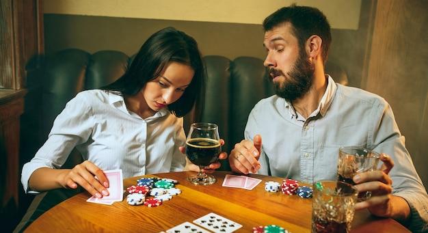 Widok z boku zdjęcie przyjaciół siedzących przy drewnianym stole. przyjaciele bawią się podczas gry w gry planszowe.